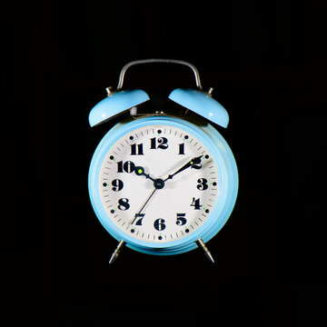 Classic table alarm clock light blue on a black background