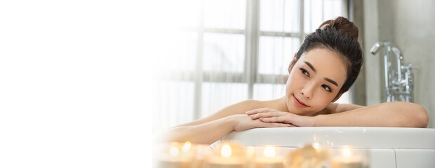 Closeup beautiful asian young  woman lying down soke in bath tub at Asian luxury spa and wellness center. Portrait of beauty woman relaxing, healthcare lifestyle concept banner.