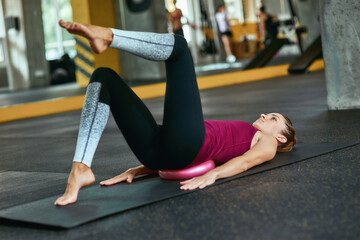 Young caucasian fitness woman in sportswear lying on yoga mat at gym and doing abs exercises, using...