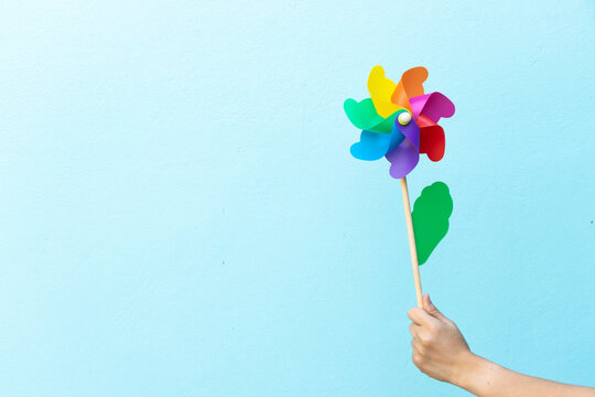 People hold colorful toy plastic turbine windmill on blue background