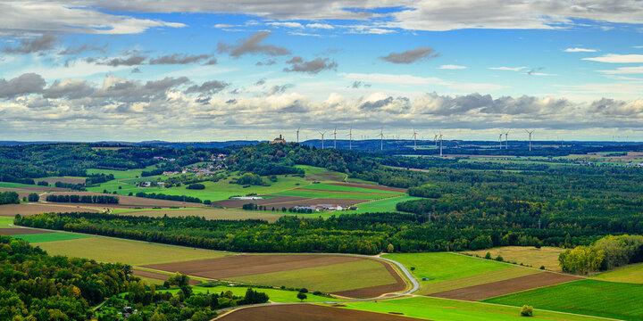 Der Blick vom Ipf am Rand des Nördlinger Ries mit Blick über Wälder und Felder in Richtung Nordwest mit Schloß Baldern und Windpark.