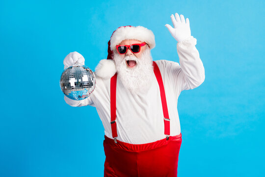 Photo of cool hipster santa claus dance x-mas christmas tradition holly discotheque hold glitter ball wear suspenders overalls headwear cap isolated over blue color background