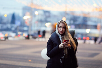 Caucasian girl woman in a long down coat in the city with a phone, the concept of safety and life in the city, communication Fotomurales