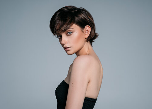 Portrait of a young beautiful brunette girl with stylish short hair