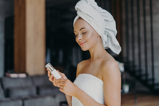 Pleased healthy woman with smooth skin, minimal makeup, holds bottle of body lotion, wrapped in bath towel, poses indoor against blurred background. Female with skin care product. Beauty concept