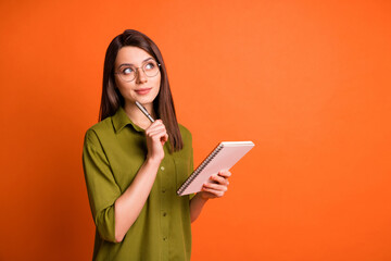 Photo portrait of thoughtful dreamy brunette girl writing with pen isolated on vivid orange color...