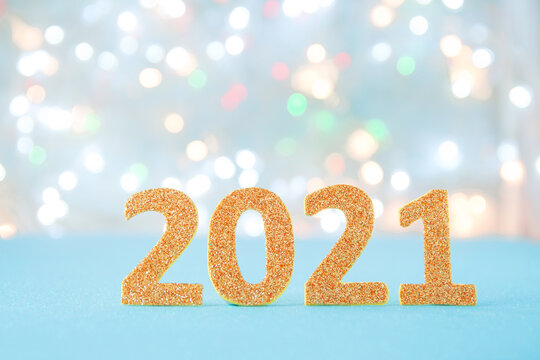 2021 gold numbers with glitter on light bokeh background. Festive greeting card fr new year with copy space