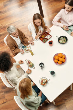 A group of five creative women of different age well-dressed sitting at a tablke together eating healty food speaking to each other