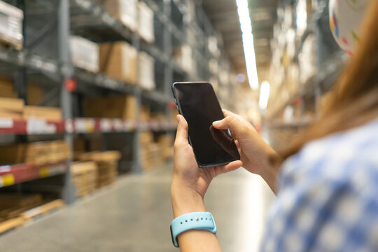 Young modern woman using touch screen mobile phone in warehouse storage.