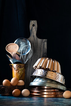 Vertical view of a stack of vintage German bundt pans surrounded by cooking utensils, eggs and a wooden cutting board