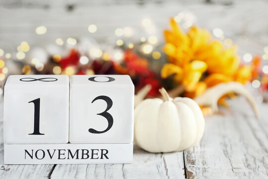 White wood calendar blocks with the date November 13th and autumn decorations over a wooden table. Selective focus with blurred background.