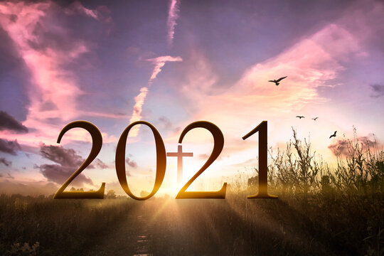 2021 concept: Wooden cross and 2021 against sunrise over grass