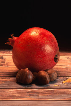 Pomegranate with chestnuts on wooden table
