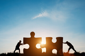 Silhouette two men pushing to connect jigsaw puzzle with sunlight and blue sky. It is symbol of business corporate teamwork to  solutions, success and strategy concept. Wall mural