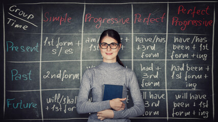 Young woman teacher or student, wearing eyeglasses and holding a book, stands in front of...