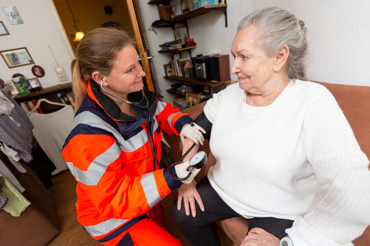 a paramedic measures an old woman's blood pressure