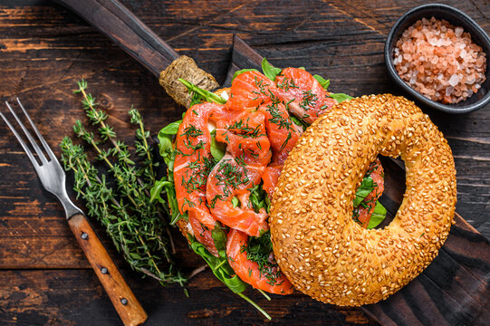 Bagels sandwich with salmon and arugula. Dark wooden background. Top view
