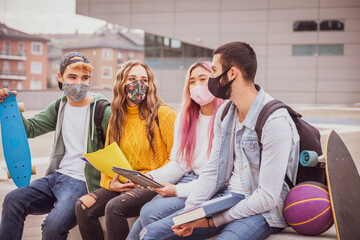 Multiethnic students sitting with mask  on the bench together in a university - Group of young...