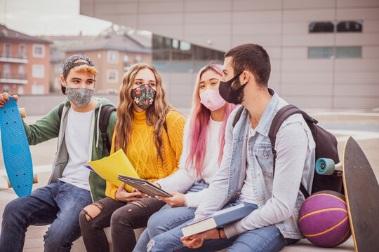 Multiethnic students sitting with mask  on the bench together in a university - Group of young teenagers studying on the bench with protective mask in pandemic covid 19 period