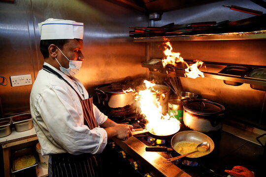A chef from the Taste of Nawab restaurant, prepares hot food packages for people in need of free school meals, in St Albans