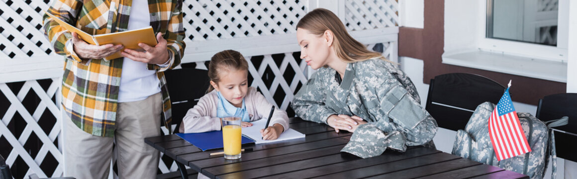 Attentive mother in military uniform sitting near daughter writing at notebook, banner