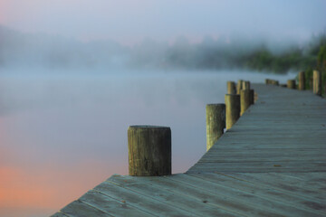 Wooden jetty in calm lake in morning with heavy fog