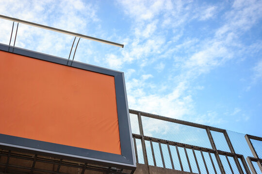 Orange isolated background on city billboard with blue cloudy sky. Promising advertising campaign concept. Copy space.