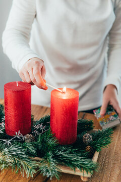 Teen girl lighting the first candle of Advent. Swiss family tradition before Christmas.