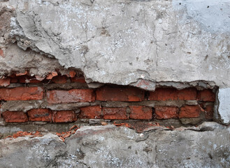 Destroyed gray plaster on a red brick wall. Background