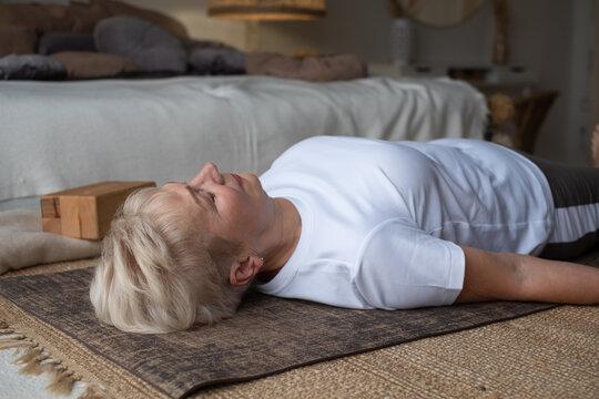 Senior caucasian woman lying on yoga mat after workout