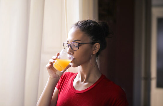 young woman drinks a orange juice