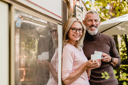 Portrait of happy successful mature couple smiling at the camera holding cups of coffee near their van