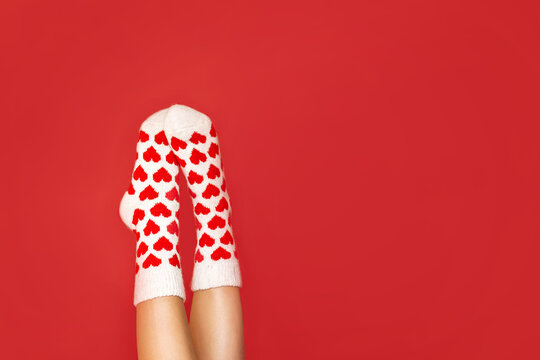 beautiful feet in warm socks with a hearts print on a red background close up.