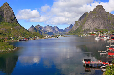 Sharp mountains, red huts and fishing boats reflected into the fjord in Reine, Lofoten Islands, Norway