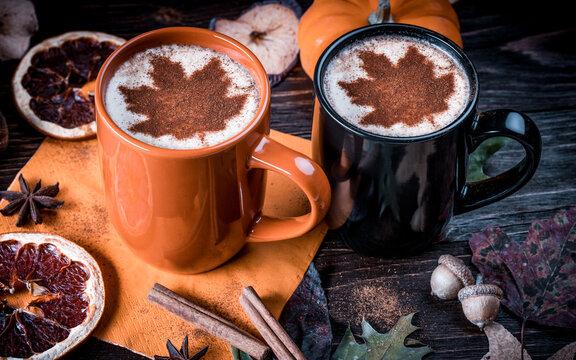 Pumpkin Spice Latte. Milk foam Decorated Maple leaf. Fall leaves, dried fruits, orange slices, acorns, star anise, pumpkins, apple, cinnamon sticks on wooden board. Autumn season.