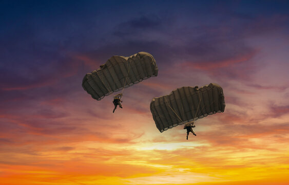Silhouette skydiver under colorful parachute on twilight sky background.