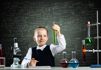 Little girl scientist examining test tube