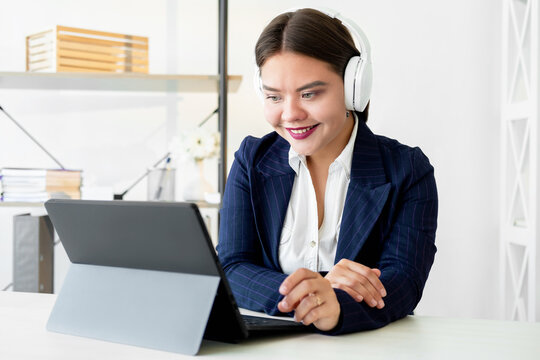Zoom videochat. Corporate webinar. Online communication. Remote job. Cheerful confident business woman discussing project using white headphones laptop working in light home office.