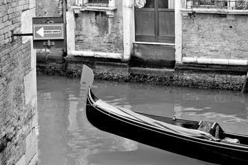 Venice, Italy, December 28, 2018 evocative black and white image of a typical Venice canal with signposts for boats gondolas and a moving gondola