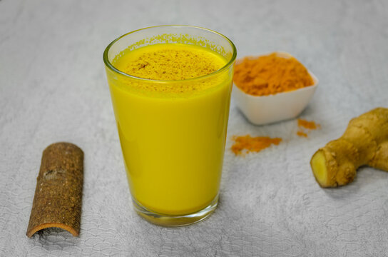Closeup of Immunity Boosting Turmeric Milk along with cinnamon, turmeric powder and ginger