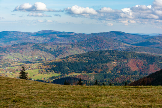 Autumn landscape of mountain hills covered with colorful forests. Zywiec Beskids.