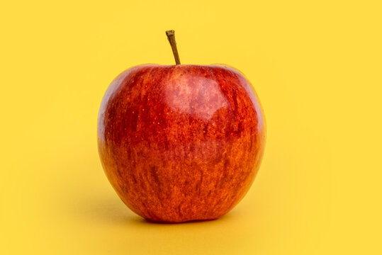 apple isolated on yellow background, autumn red fruit of the variety named fuji