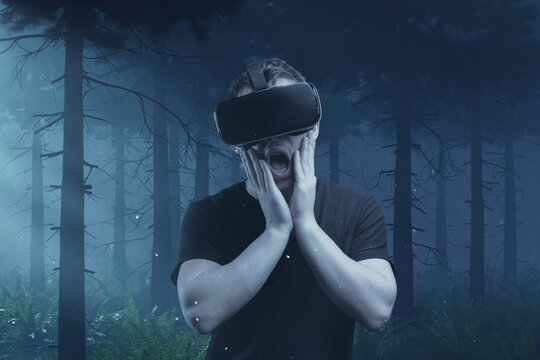 scary young man getting experience with vr device playing horror game in front of foggy forest