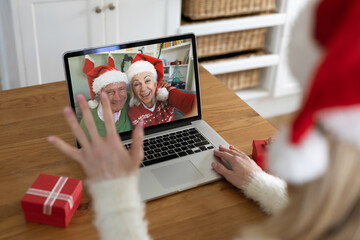 Rear view of woman in santa hat waving while having a videocall with senior couple in santa hats on