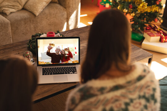 Rear view of woman and son having a videocall with couple in santa hats toasting on laptop at home