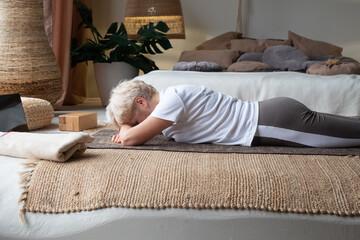 senior woman relaxes in yoga asana Makarasana or crocodile pose