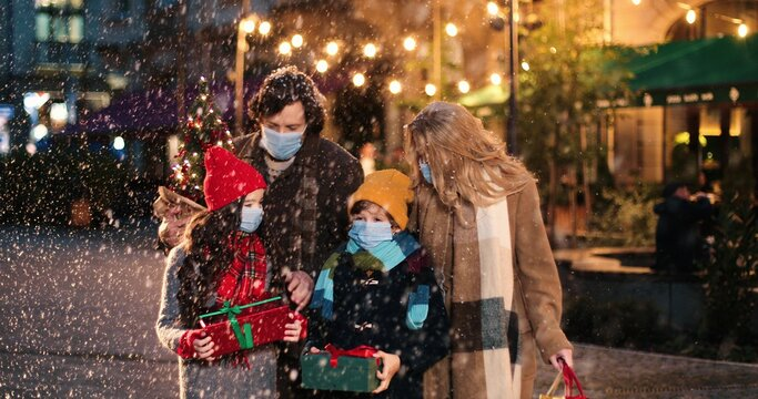 Portrait of Caucasian happy family walking with presents outdoors. Joyful kids with parents on street in city with little new year tree while snowing. Holiday lights and decoration. Christmas concept