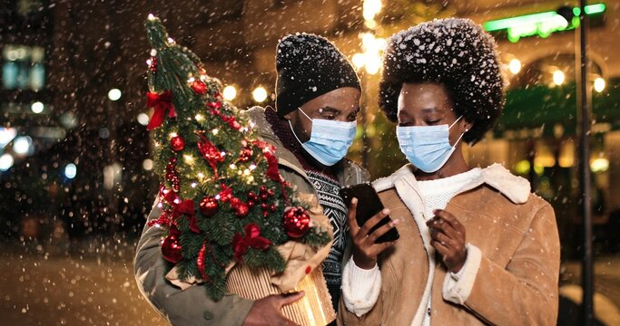 Close up of cheerful family standing in snowy city and talking while snowing. Young African American happy female tapping on smartphone outdoors with man with little Christmas tree. Winter concept