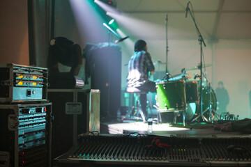 Fototapeta grający na koncercie muzyk widoczny od strony konsoli nagłośnieniowej