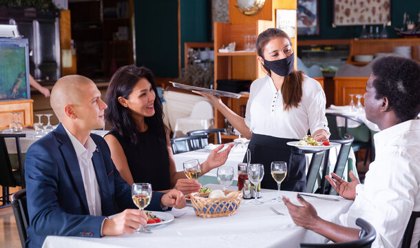 Hospitable waitress wearing face protective mask bringing ordered meals to guests. New normal restaurant concept in coronavirus pandemic ..